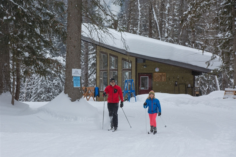 Elk Valley Nordic Centre - Father & daughter xc skiing from warming hut