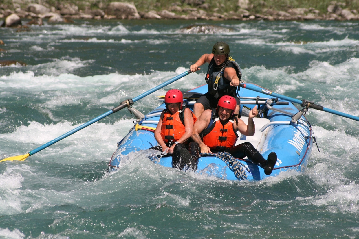 Guests riding the bull on Fernie's classic white water rafting trip